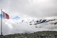 Panorama della montagna delle alpi con la bandiera dello svizzero nel giorno nuvoloso Immagine Stock