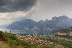 Panorama della polizia del lago, del villaggio Torbole della riva del lago e delle montagne con le nuvole di tempesta scure, Ital Fotografie Stock