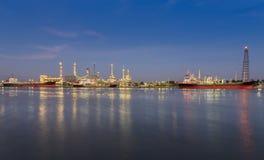 Panorama della raffineria di petrolio a penombra con la riflessione del fiume Fotografie Stock Libere da Diritti
