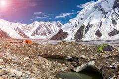 Panorama delle alte montagne con le tende rosse e verdi sulla moraine del ghiacciaio e sul Sun brillante Immagine Stock
