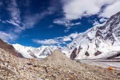 Panorama delle alte montagne con le tende rosse ed arancio sulla moraine del ghiacciaio Fotografia Stock