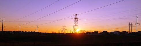 Panorama delle linee elettriche ad alta tensione di distribuzione pilone a sunse Fotografie Stock Libere da Diritti