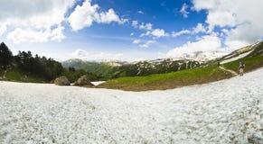 Panorama delle montagne della neve di estate con le viandanti sul percorso Immagine Stock Libera da Diritti
