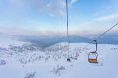 Panorama delle montagne di inverno con gli ski-lift Immagine Stock