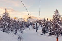 Panorama delle montagne di inverno con i pendii e gli ski-lift dello sci Fotografia Stock