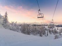 Panorama delle montagne di inverno con i pendii e gli ski-lift dello sci Fotografie Stock Libere da Diritti