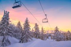 Panorama delle montagne di inverno con i pendii e gli ski-lift dello sci Fotografie Stock