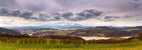 Panorama delle montagne nevose di Tatra della molla Behin del villaggio e del lago Fotografia Stock