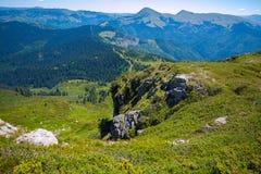 Panorama delle montagne verdi contro il cielo blu Immagine Stock