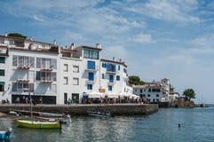 Panorama der Architektur in Cadaques mit Terrassen von Restaurants und von Booten machte nahe der Küste fest stockfotografie