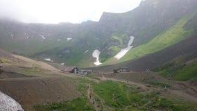 Panorama der Berge und der Aibga-Kante mit tiefen Wolken Überreste des Schnees und des frischen grünen Grases auf den Bergen nahe stockfoto