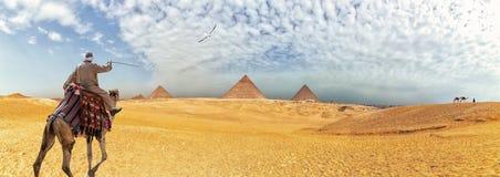 Panorama der Giseh-Pyramiden und des Beduinen, die ein jellabiya auf einem Kamel, Ägypten tragen lizenzfreie stockfotos
