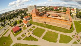 Panorama der Stadt von Lida mit einem Schloss Schattenbild des kauernden Geschäftsmannes Lizenzfreie Stockfotografie