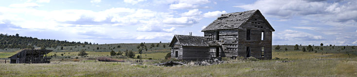 Panorama of Derelict Homestead and Horse Barn. Panoramic view of back of 19th century homestead house with horse barn and windmill.  Measures 55.296 x 12.05 Stock Images