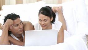 Panorama des couples dans le lit utilisant un ordinateur portable banque de vidéos