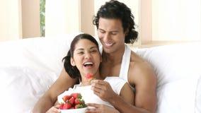 Panorama des couples se reposant dans le lit mangeant des fraises clips vidéos