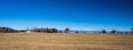 Panorama des Feldes in West-Colorado mit Bauernhöfen und des Schnees mit einer Kappe bedeckt Lizenzfreie Stockfotografie