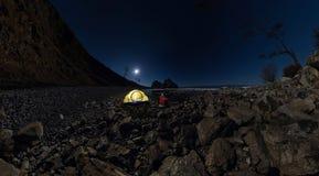 Panorama des Mannes am Zelt auf Steinstrand auf Ufer von See Baika Stockbild