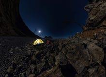 Panorama des Mannes am Zelt auf Steinstrand auf Ufer von See Baika Lizenzfreie Stockfotografie