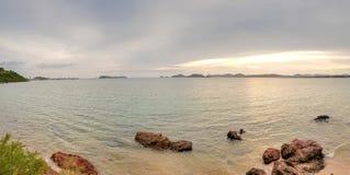 Panorama des Meerblicks mit natürlichem Felsenstrand wenn Sonnenuntergangzeit lizenzfreie stockfotos