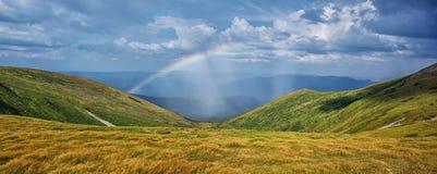 Panorama des Regenbogens in den Bergen Stockbilder