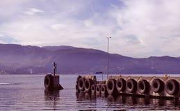 Panorama des Sees mit dem Pier, der mit Reifen bedeckt wird stockfoto