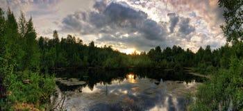 Panorama des Sonnenuntergangs über düsterem Frühlingssee Stockbilder