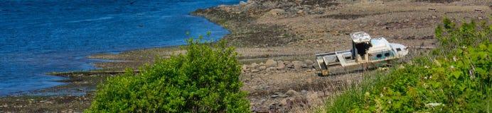 Panorama des Wassers und des auf den Strand gesetzten aufgegebenen Fischerbootes stockbild