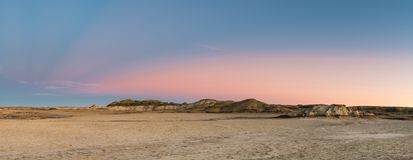 Sunset panorama of a flat, barren desert with colorful peaks and hills. Panorama of the desert landscape and hills of the Bisti Badlands of New Mexico at sunset royalty free stock images