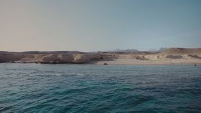 Panorama of a deserted beach against the background of the rocky mountains. Crystal clear blue ocean water. Sunset.  stock footage