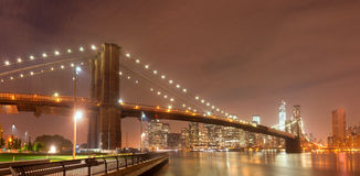 Panorama di notte di New York con il ponte di Brooklyn Immagine Stock