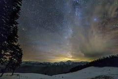 Panorama di notte di inverno della montagna dopo il tramonto Picchi di montagna lunghi ripidi della cresta, neve profonda in vall fotografia stock libera da diritti