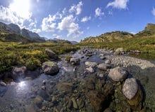 Panorama di paesaggio della montagna con il prato, situato nella valle Fotografia Stock
