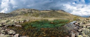 Panorama di piccolo lago dell'alta montagna Immagine Stock