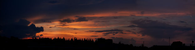 Panorama di tramonto sopra la città con le tonalità e le nuvole rosse Fotografie Stock Libere da Diritti