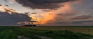 Panorama di un granaio e degli stormclouds illuminati dalla luce del tramonto fotografie stock