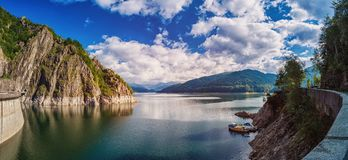 Panorama di un lago della montagna vicino alla diga Bello cielo blu con le nuvole Immagine Stock Libera da Diritti