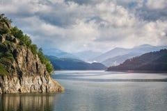 Panorama di un lago della montagna vicino alla diga Bello cielo blu con le nuvole Fotografia Stock Libera da Diritti