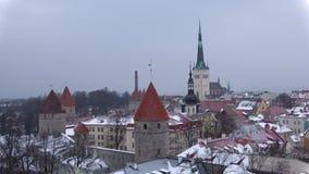 Panorama di vecchia città che domina la chiesa delle precipitazioni nevose della st Olaf di Oleviste a marzo Tallinn, Estonia stock footage