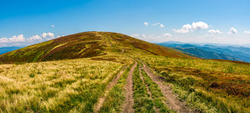 Panorama with dirt road through mountain ridge Royalty Free Stock Photography