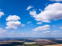 Panorama do ar nos prados luxúrias e nos campos com lotes coloridos das colheitas agrícolas crescidas sob o céu aberto fora imagens de stock royalty free
