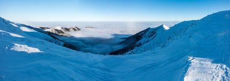 Panorama do cume da montanha do inverno acima das baixas nuvens Fotos de Stock