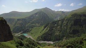 Panorama do desfiladeiro da montanha que negligencia as rochas, os montes dos picos de montanha cobertos com o denso e as árvores filme