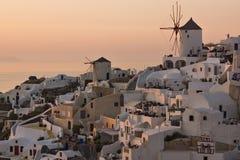 Panorama do por do sol sobre os moinhos de vento brancos na cidade de Oia e panorama à ilha de Santorini, Thira, Grécia fotografia de stock