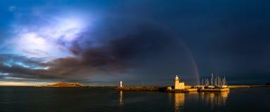 Panorama do porto de Howth no condado Dublin sob um céu nebuloso tormentoso dramático com um arco-íris imagens de stock
