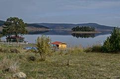 Panorama do reservatório da represa de Batak com a ilha na água e a clareira litoral do outono, casa de campo, floresta, monte em fotos de stock royalty free