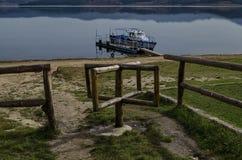 Panorama do reservatório da represa de Batak com o passageiro-navio na água, na clareira litoral do outono e no fense de madeira foto de stock royalty free