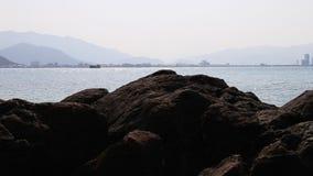 Panorama do seascape com o oceano das pedras e o sity azuis da skyline filme