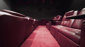 Panorama do teatro com as poltronas do couro do conforto, cinema sem povos, cinema antes da sessão, vip do cinema video estoque
