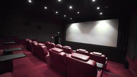 Panorama do teatro com as poltronas do couro do conforto, cinema sem povos, cinema antes da sessão, vip do cinema filme